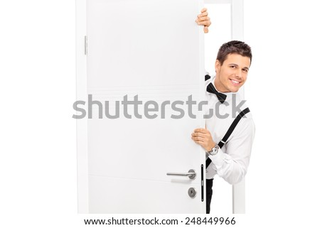 Elegant young guy posing behind a door isolated on white background - stock photo