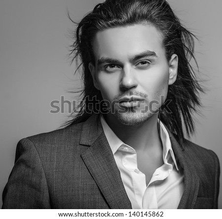 Elegant young handsome long-haired man. Black-white fashion portrait. Elegant young handsome long-haired man. Studio fashion portrait.  - stock photo