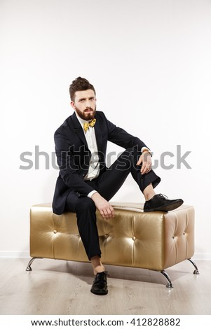 Elegant young handsome man in black classic costume. Studio fashion portrait. Isolated on white. Sit on luxury gold sofa.