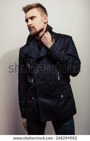 Elegant young handsome man in black coat. Studio fashion portrait.  - stock photo