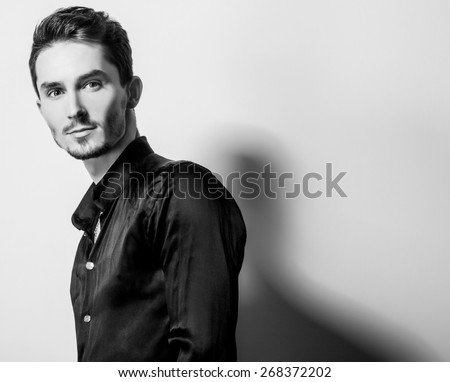 Elegant young handsome man in black silk shirt. Black-white studio fashion portrait.  - stock photo