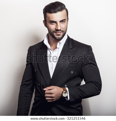 Elegant young handsome man in classic black costume. Studio fashion portrait.  - stock photo