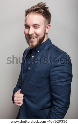 Elegant young handsome man in classic dark blue costume. Studio fashion portrait.