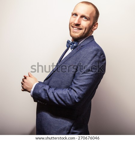 Elegant young handsome man in dark blue costume & bow tie. Studio fashion portrait. - stock photo