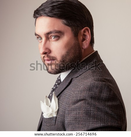 Elegant young handsome man in grey costume. Studio fashion portrait. - stock photo