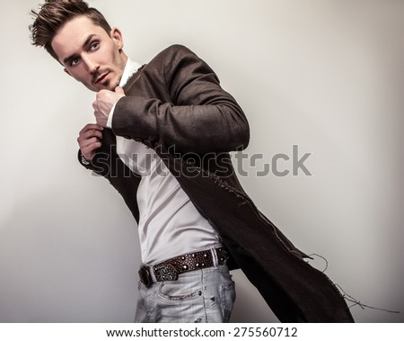 Elegant young handsome man in long stylish coat. Studio fashion portrait.  - stock photo