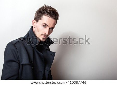 Elegant young handsome man in long stylish dark blue coat. Studio fashion portrait. - stock photo