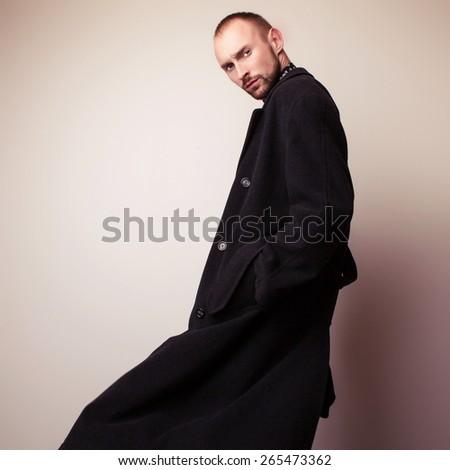 Elegant young handsome man in long wool coat. Studio fashion portrait. - stock photo