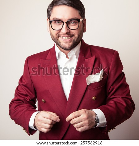 Elegant young handsome man in luxury red costume. Studio fashion portrait. - stock photo