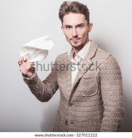 Elegant young handsome man in stylish beige costume. Studio fashion portrait.