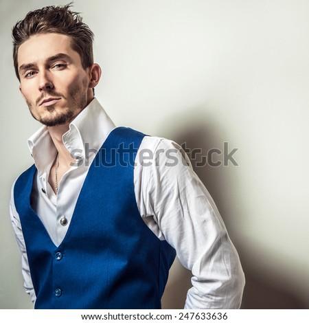 Elegant young handsome man in white shirt & vest. Studio fashion portrait. - stock photo