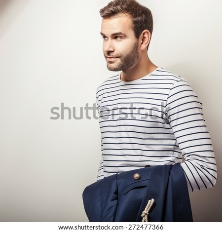 Elegant young handsome & positive man with dark blue jacket. Bright studio fashion portrait.