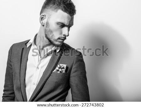 Elegant young handsome serious man in classic costume. Black-white studio fashion portrait.  - stock photo
