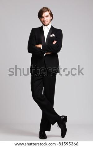 elegant young man in black tuxedo, full body shot,  studio shot - stock photo