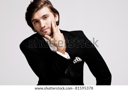 elegant young man in black tuxedo, portrait, studio shot - stock photo