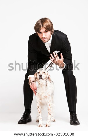 elegant young  man in tuxedo and his dog, studio shot - stock photo