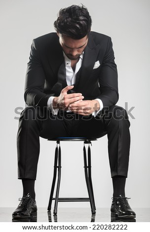 Elegant young man in tuxedo looking down while sitting on a stool, on grey studio background. - stock photo