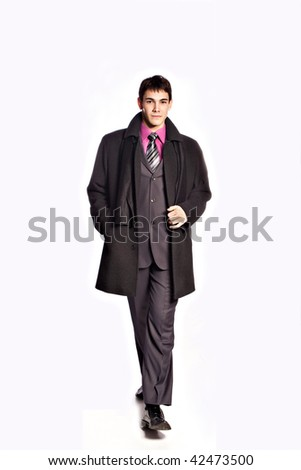 elegant young man in winter suit and coat studio on white - stock photo