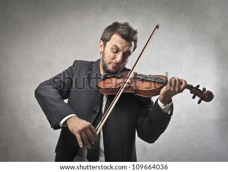 Elegant young man playing the violin - stock photo
