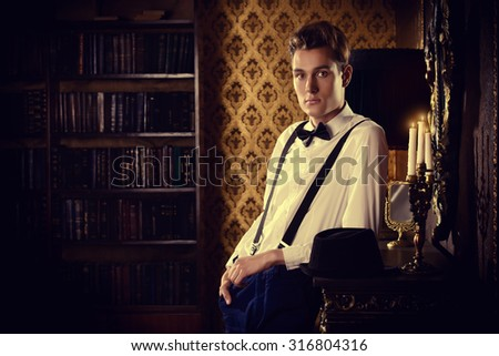 Elegant young man stands by the fireplace in a room with classic interior. Fashion shot. - stock photo