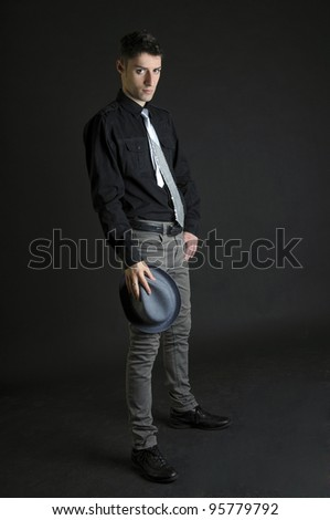 Elegant young man with hat in his hand on black background - stock photo
