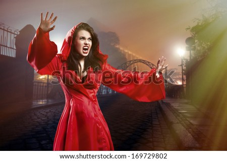 Elegant young witch in a red clothes cast magic spell in city
