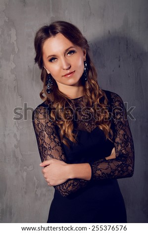 Elegant young woman in black lace dress with long curly hair smiling at the camera