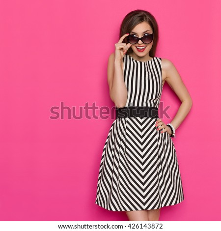 Elegant young woman in striped dress looking over sunglasses at copy space and smiling. Three quarter length studio shot on pink background. - stock photo