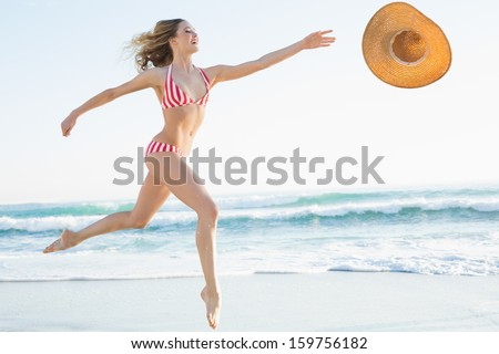 Elegant young woman jumping on beach trying to catch a straw hat - stock photo