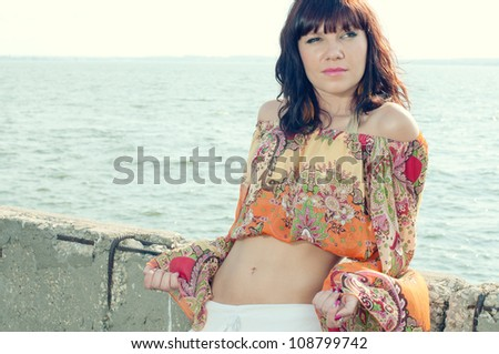 Elegant young woman relaxing near the shore during summer time - stock photo