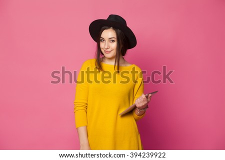 Elegant young woman using tablet leaning to pink wall, looking at camera. Hipster girl holding a tablet computer - stock photo