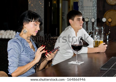 Elegant young woman with manicured red nails sitting texting on her mobile at the bar counter in a nightclub, side view - stock photo