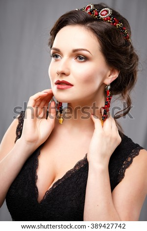 Elegant young woman with perfect makeup and hair style in a black dress. Beauty fashion portrait with accessories