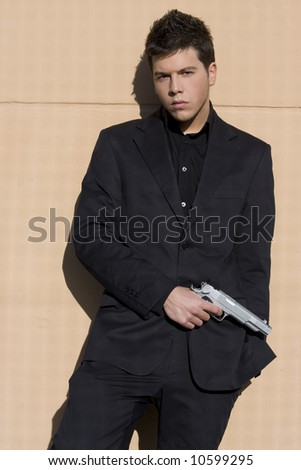 Elegantly dressed armed man on a wall - stock photo