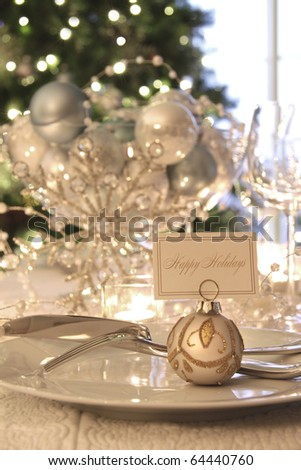 Elegantly lit holiday dinner table with focus on place card - stock photo