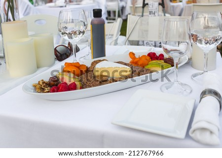 Elegantly served cheese, nuts and fruits on the picnic table outdoors - stock photo