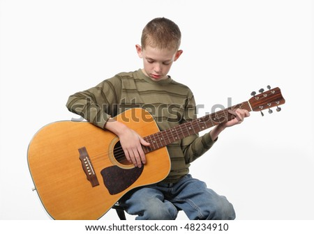 elementary age child sitting and playing a large acoustic guitar - stock photo