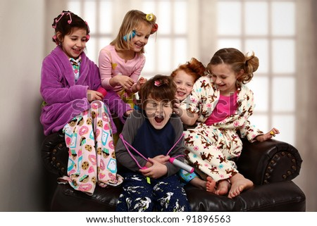 Elementary age girls at slumber party torture brother with hair rollers and makeup. - stock photo