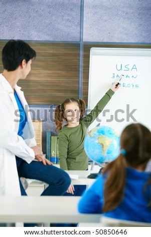 Elementary age schoolgirl at whiteboard answering to teacher in geography lesson. - stock photo