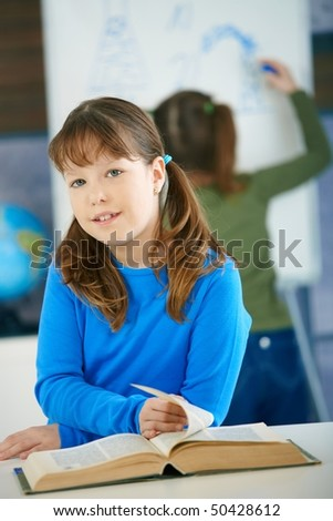 Elementary age schoolgirl looking at book in science class in primary school classroom.
