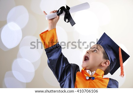 Elementary boy proudly wearing his graduation cap and gown over bokeh background. - stock photo