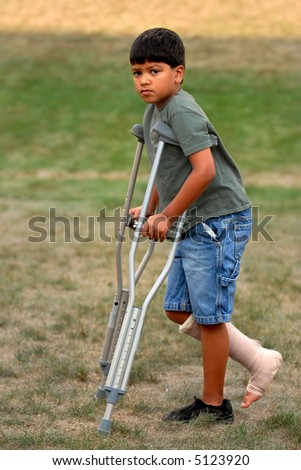 Elementary boy walking on crutches with his leg and foot bandaged-wrapped. - stock photo