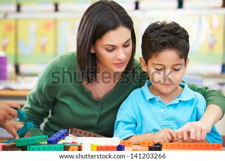 Elementary Pupil Counting With Teacher In Classroom - stock photo