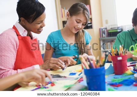 Elementary pupil in art class with teacher - stock photo