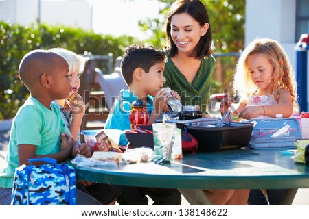 Elementary Pupils And Teacher Eating Lunch - stock photo
