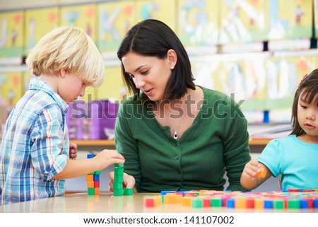 Elementary Pupils Counting With Teacher In Classroom - stock photo