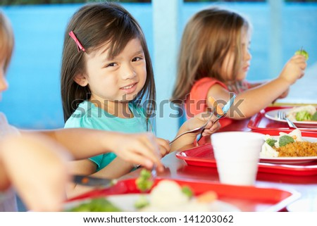 Elementary Pupils Enjoying Healthy Lunch In Cafeteria - stock photo