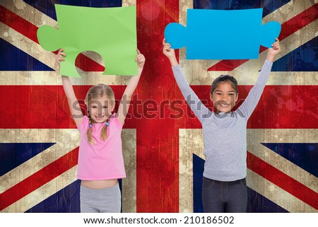 Elementary pupils holding jigsaw pieces against union jack flag in grunge effect - stock photo