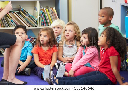 Elementary Pupils In Classroom Working With Teacher - stock photo