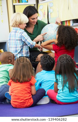 Elementary Pupils In Geography Class With Teacher - stock photo